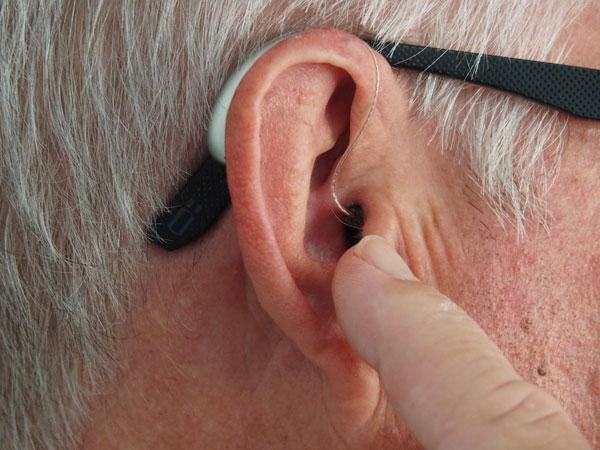 A man touching his ear